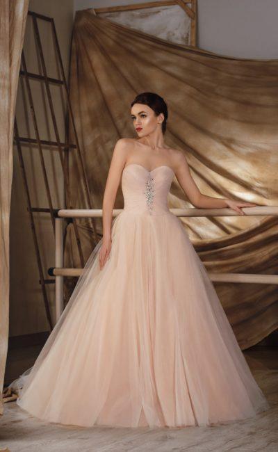 Кремово-персиковое свадебное платье пышного кроя с декором из драпировок и стразов.