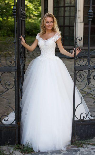 Классическое свадебное платье пышного кроя с округлым декольте и аппликациями из кружева.