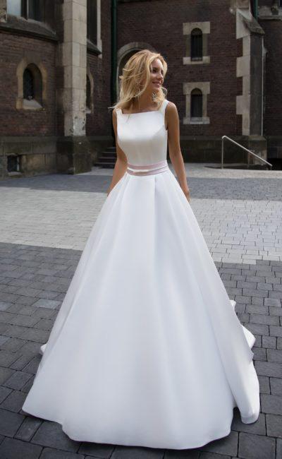 Элегантное свадебное платье из глянцевой атласной ткани, с вырезом каре и узким поясом.