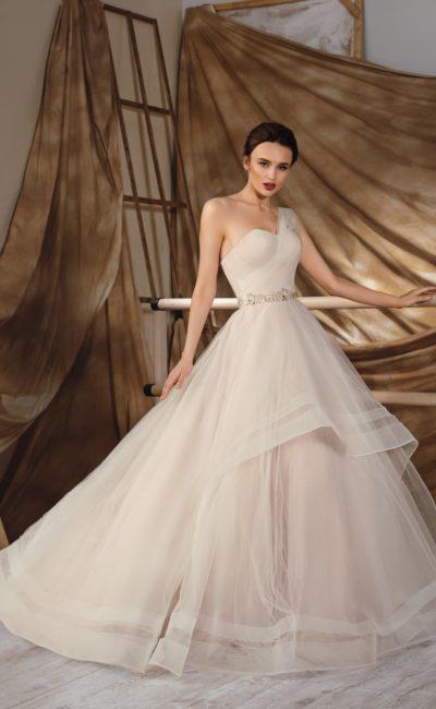 Бежевое свадебное платье с многоярусной юбкой со шлейфом и открытым асимметричным лифом.