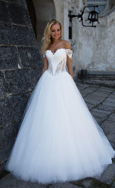 Пышное свадебное платье с полупрозрачными боками корсета и декольте с бретелями на предплечьях.