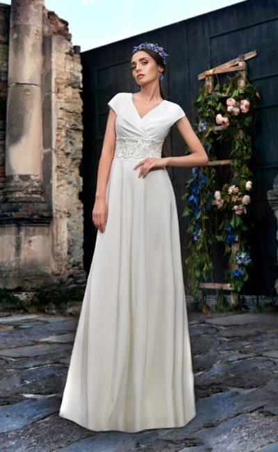 Прямое свадебное платье с глубоким декольте и широким поясом, украшенным вышивкой.