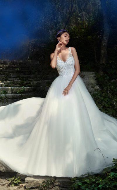 Торжественное свадебное платье с пышным шлейфом и кружевной отделкой облегающего верха.