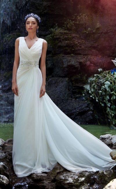 Прямое свадебное платье с V-образным декольте, широким поясом и отделкой из драпировок.
