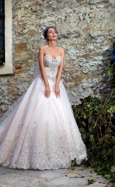 Свадебное платье А-силуэта с открытым корсетом, покрытым роскошным шитьем из стразов.