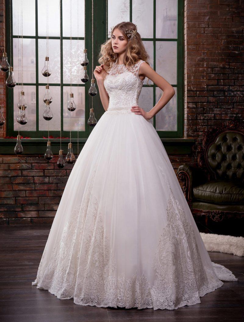 Великолепное свадебное платье с объемным подолом и закрытым верхом, украшенным аппликациями.