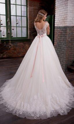 Свадебное платье пышного кроя с закрытым верхом, выполненное в легком розовом оттенке.