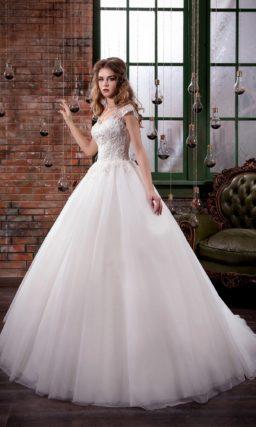Пышное свадебное платье с кружевной отделкой верха с широкими бретелями и небольшим декольте.