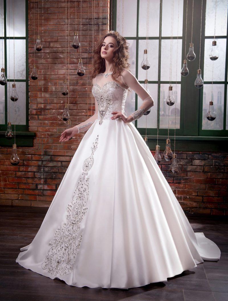 Атласное свадебное платье пышного кроя с роскошной серебристой вышивкой и прозрачным рукавом.