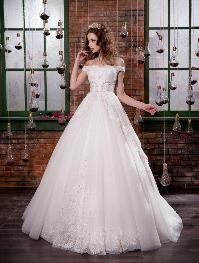 Открытое свадебное платье с портретным декольте и многослойной юбкой со шлейфом.