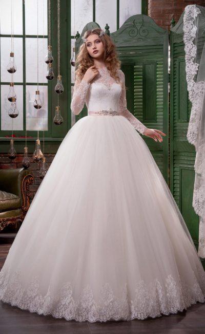 Пышное свадебное платье с длинными кружевными рукавами и узким поясом из розового атласа.