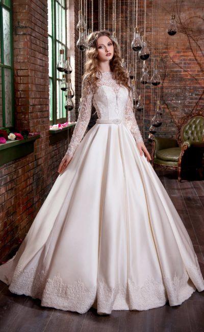 Атласное свадебное платье с изысканной юбкой А-силуэта и рукавами из плотного кружева.