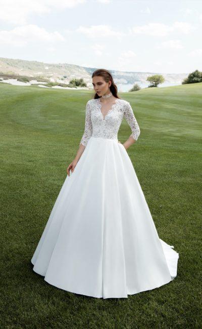Элегантное свадебное платье с роскошной юбкой и кружевным лифом с V-образным вырезом.