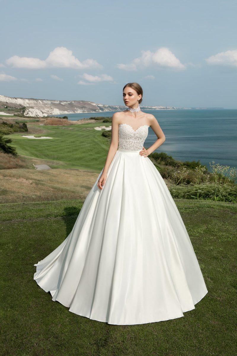Потрясающее свадебное платье с пышной атласной юбкой и чувственным открытым корсетом.