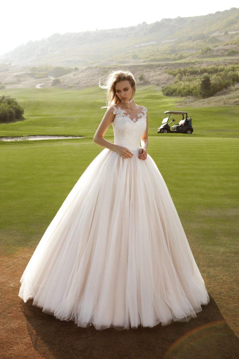 Пышное свадебное платье с многослойным подолом с вертикальными складками и кружевным верхом.