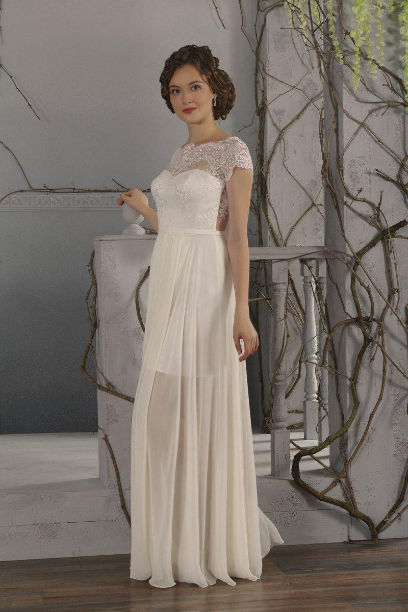 Стильное свадебное платье прямого кроя с широким вырезом, оформленным кружевом, и полупрозрачной юбкой.