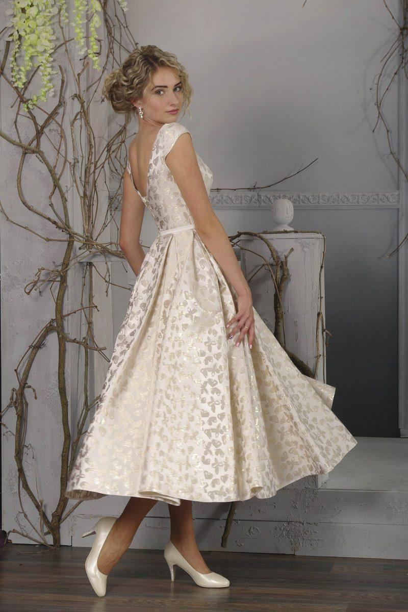 Необычное свадебное платье чайной длины с глянцевым рисунком и вырезом на спинке.
