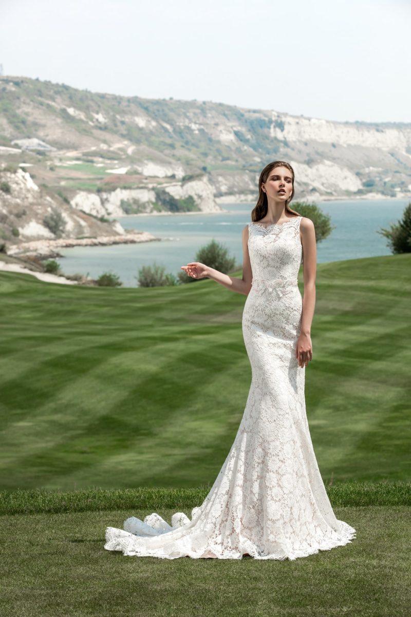 Прямое свадебное платье с фигурным вырезом бато и плотной кружевной отделкой по всей длине.