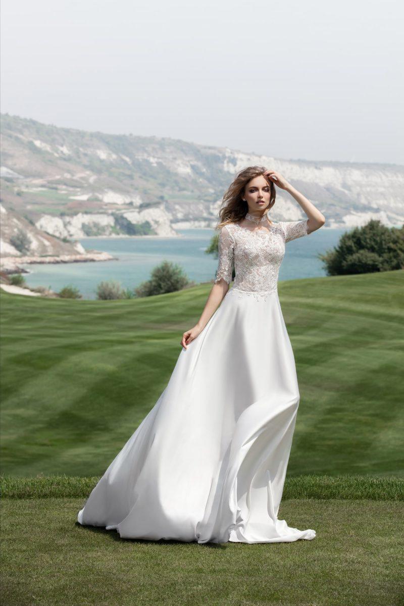 Женственное свадебное платье с атласной юбкой и закрытым кружевным верхом с рукавом три четверти.