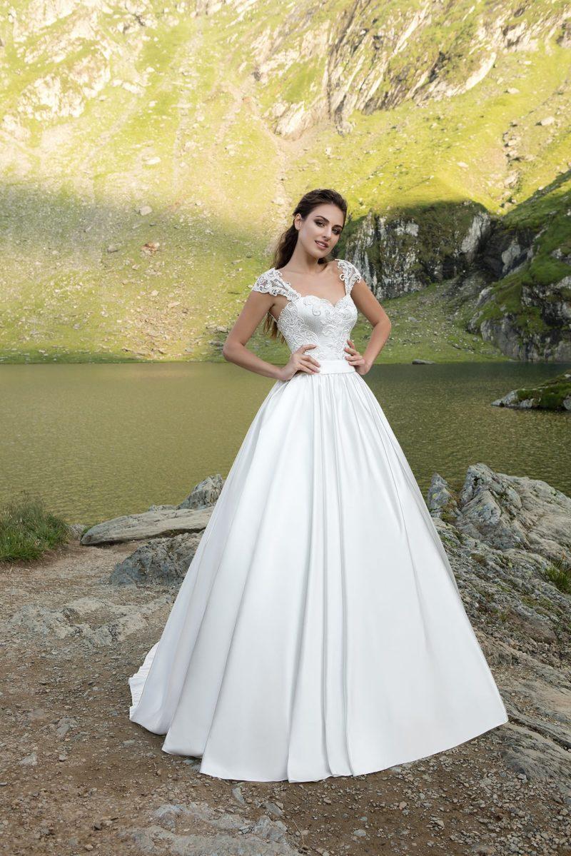 Пышное свадебное платье с роскошной атласной юбкой и коротким кружевным рукавом.