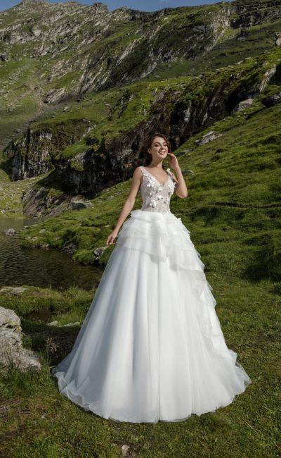 Пышное свадебное платье с облегающим верхом и многоярусными оборками по подолу.