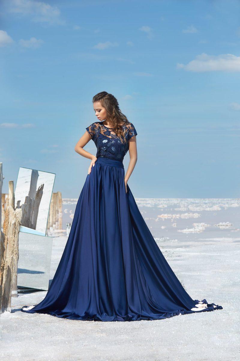 Синее вечернее платье с кружевным верхом и коротким рукавом.