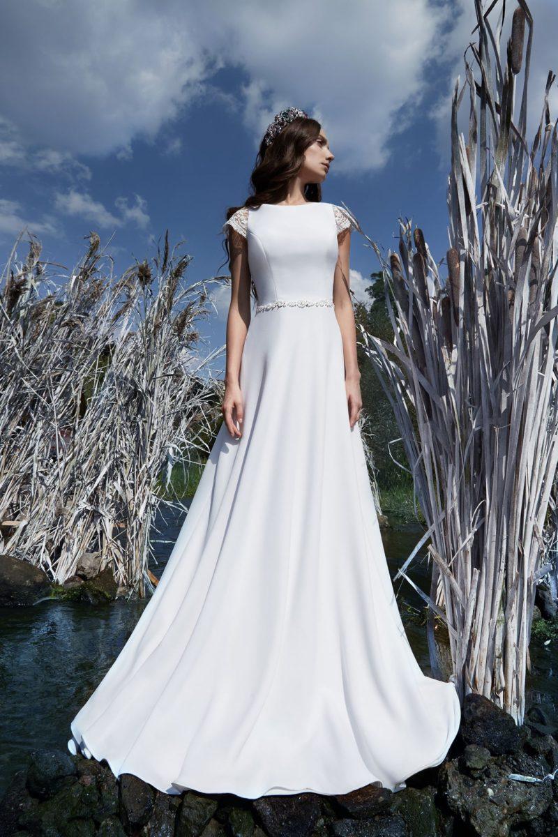 Роскошное свадебное платье из плотной атласной ткани с короткими кружевными рукавами.