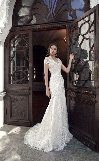Облегающее свадебное платье с коротким кружевным рукавом.