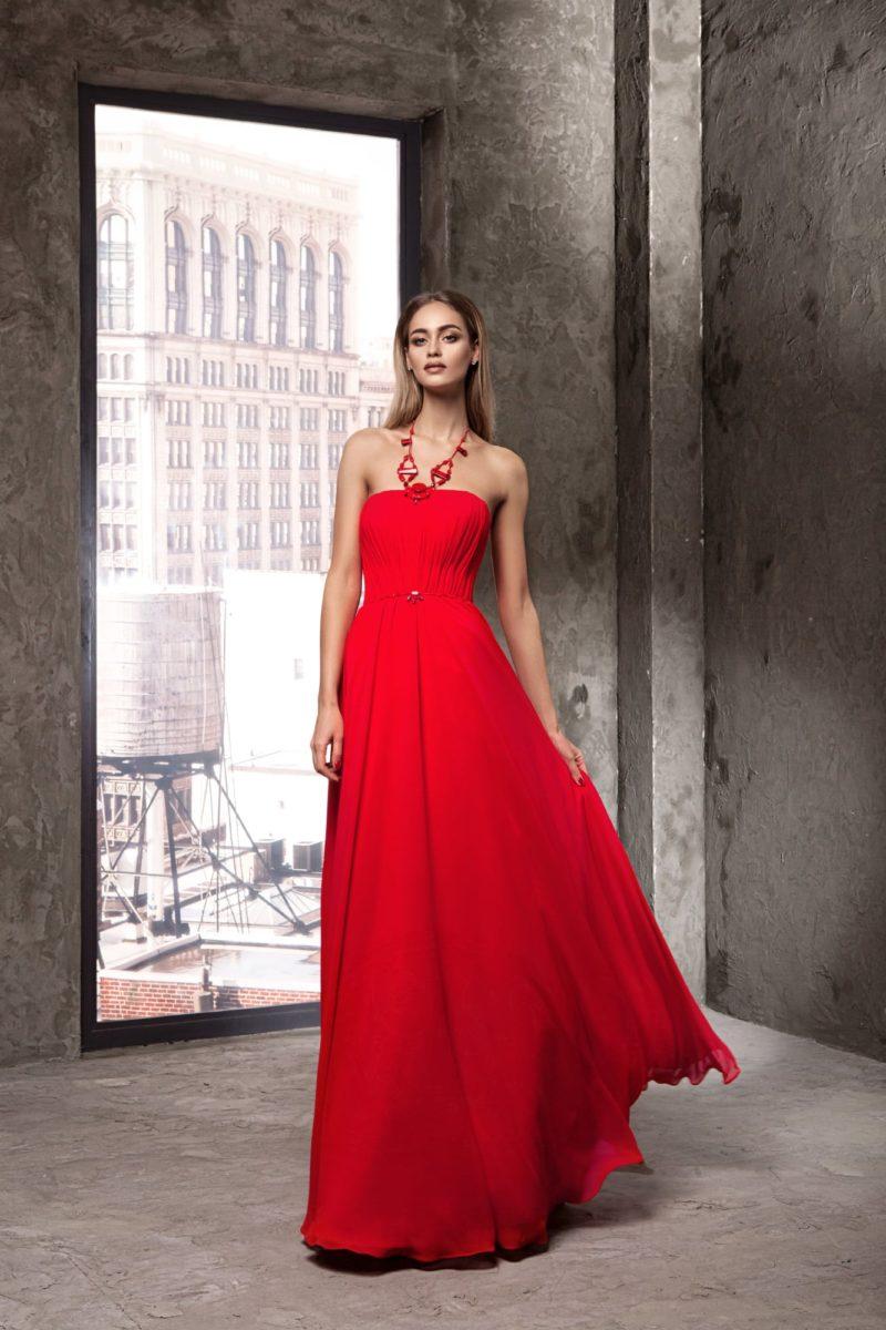 Открытое вечернее платье прямого кроя насыщенного красного цвета.