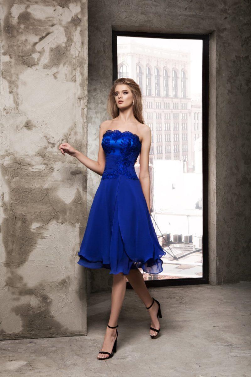 Короткое вечернее платье синего цвета с кружевной отделкой.