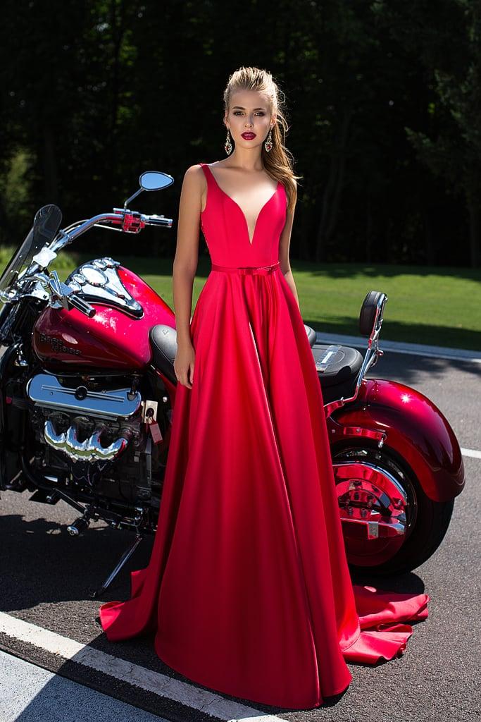 Алое вечернее платье с глубоким декольте и пышной юбкой со шлейфом.