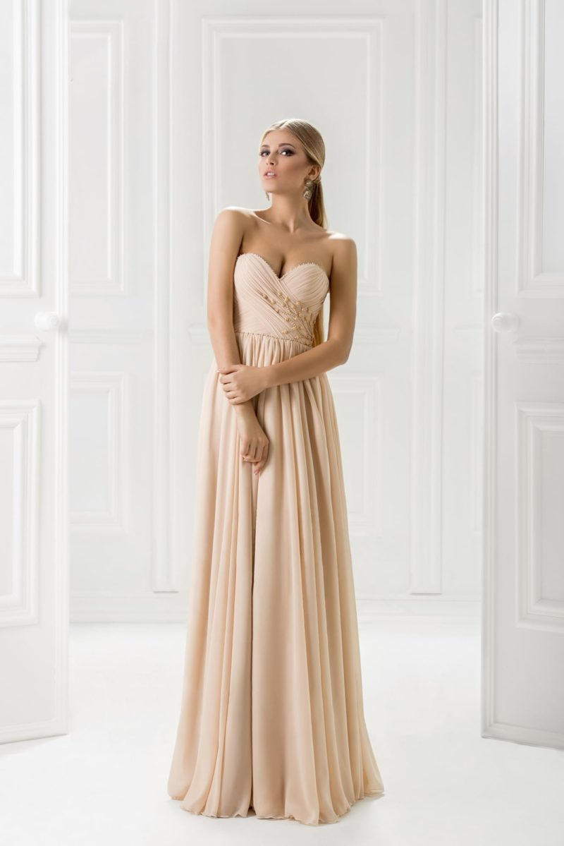 Бежевое вечернее платье с прямой юбкой и отделкой драпировками.