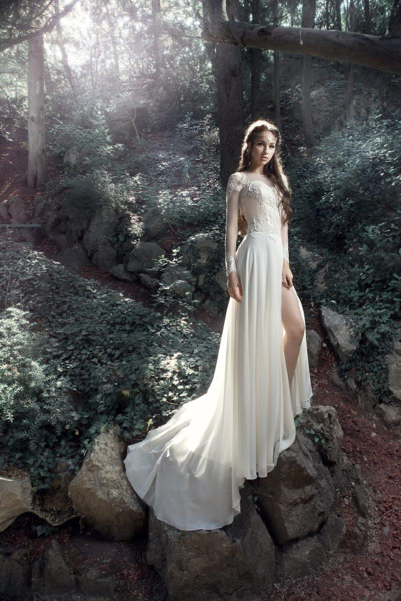 Прямое свадебное платье с высоким разрезом на юбке и вырезом на спинке.