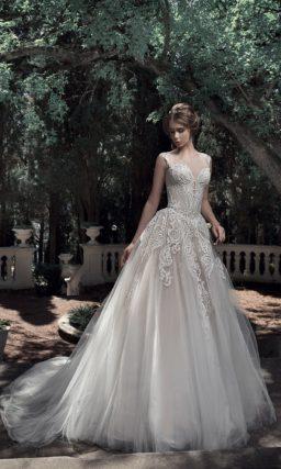 Пышное свадебное платье кремового цвета с многослойной юбкой.