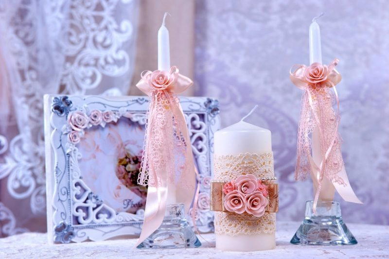 Белые свадебные свечи с розовой отделкой лентами и бутонами.