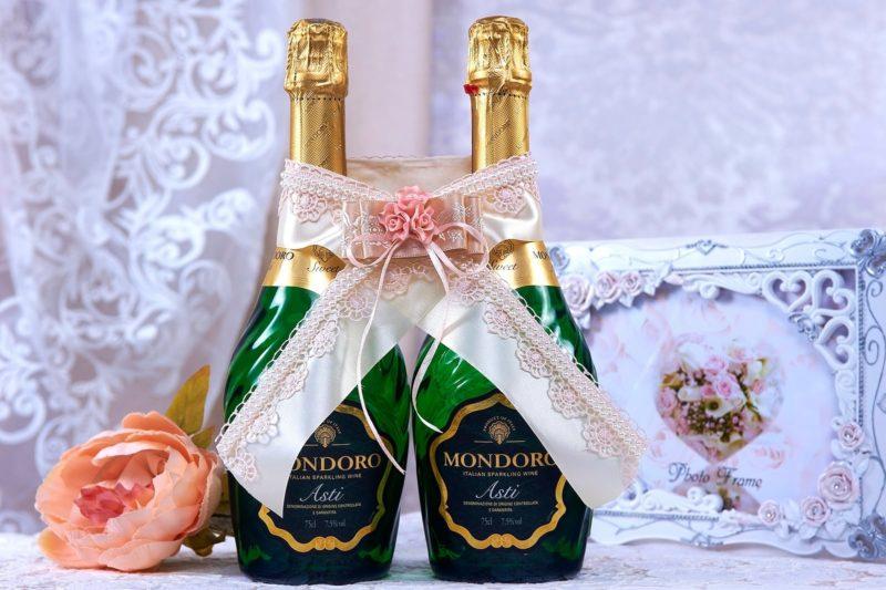 Украшение на шампанское из кружева и атласа в кремовых тонах.