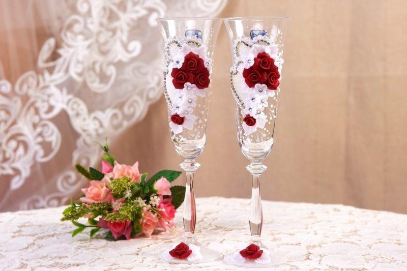 Свадебные фужеры, изящно декорированные бутонами и кружевом.
