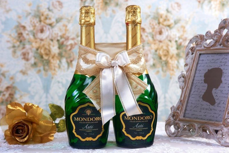 Золотистое атласное украшение на шампанское, декорированное бантом.