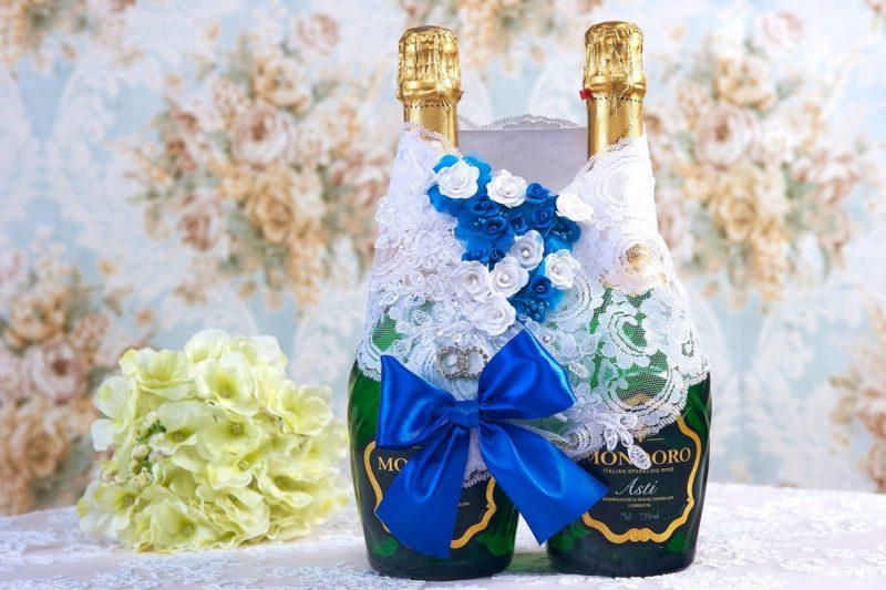 Кружевное украшение на шампанское с голубым атласным бантом.