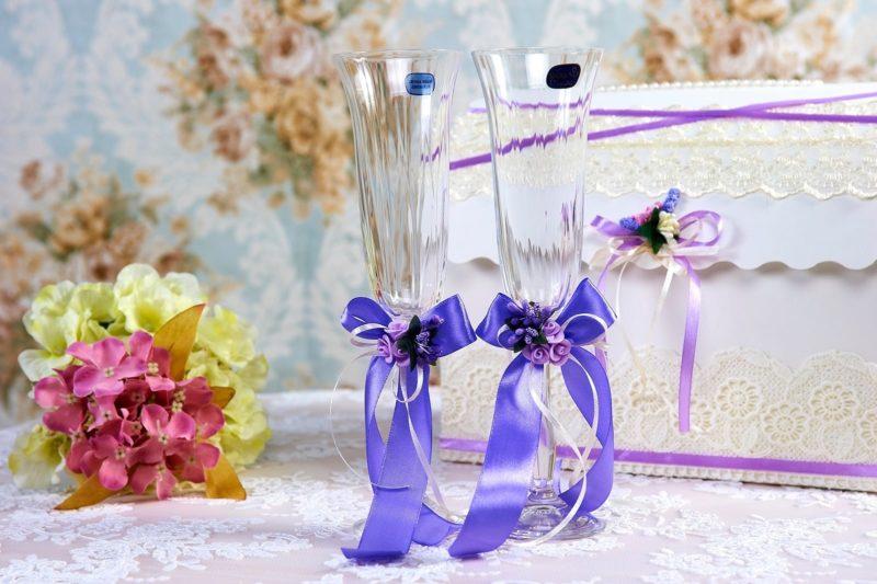 Прозрачные свадебные фужеры с голубыми атласными бантами.