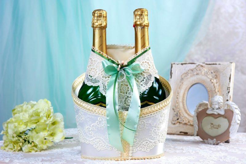 Украшение на шампанское из белого кружева с салатовым атласом.