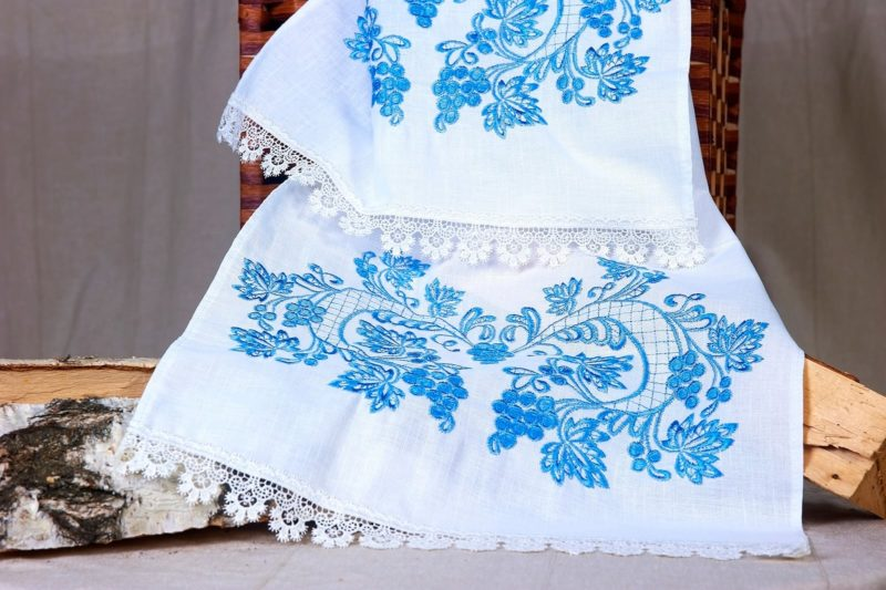 Белый свадебный рушник, декорированный голубой вышивкой.