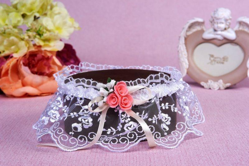 Романтичная кружевная подвязка с небольшими розовыми бутонами.