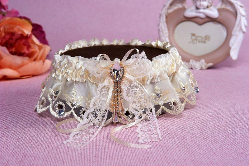Атласная подвязка кремового цвета, украшенная лентой и кружевом.