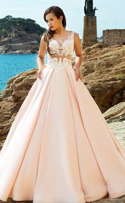 Кремовое свадебное платье с невероятно пышной юбкой и кружевным декором прозрачного верха.