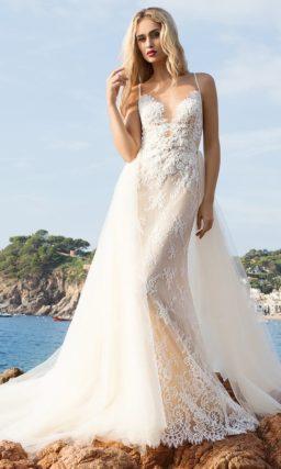Прямое свадебное платье бежевого оттенка с белым кружевом и тонкой верхней юбкой.