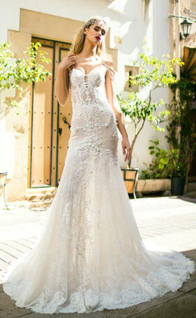 Фактурное свадебное платье из полупрозрачного кружева, изящно облегающего фигуру.