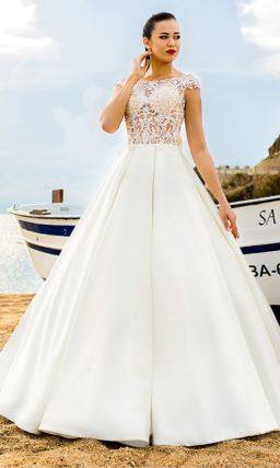 Атласное свадебное платье с вертикальными складками на пышной юбке и кружевным лифом.