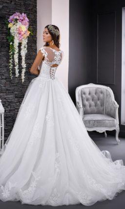 Пышное свадебное платье с полупрозрачной спинкой, декорированное кружевными аппликациями.