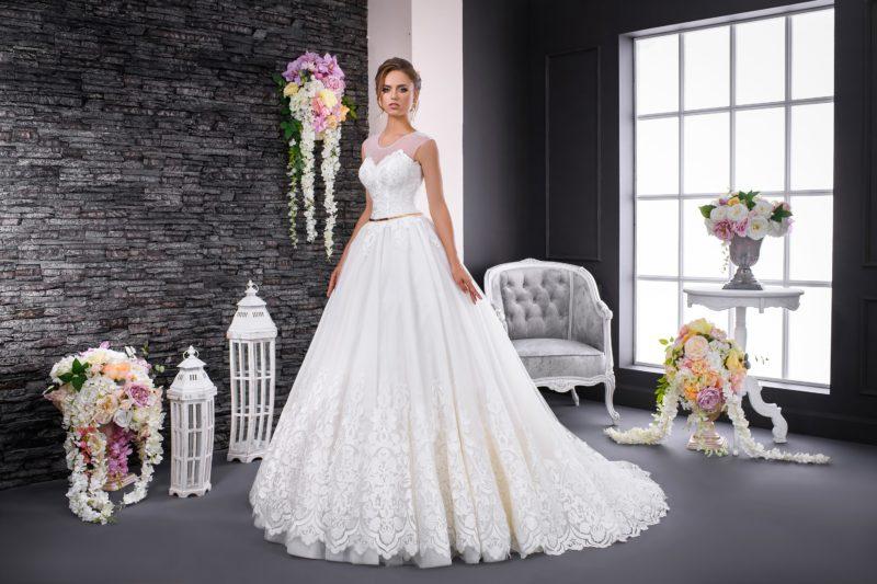 Эффектное свадебное платье с пышной юбкой со шлейфом, украшенное кружевным узором.